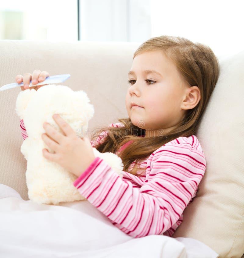 A menina está penteando seu urso de peluche imagem de stock royalty free