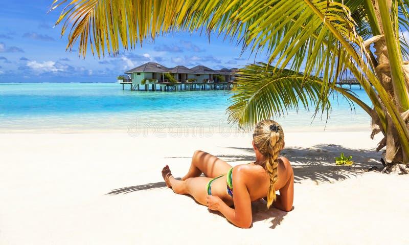 A menina está relaxando na praia do oceano foto de stock royalty free