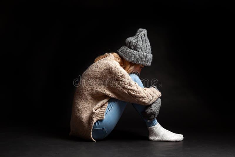 A menina está sentando-se apenas no assoalho em um fundo preto do vazio que abraça seus pés com suas mãos e deixando cair a imagens de stock