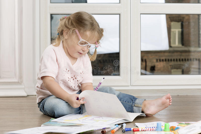 A menina está sentando-se em um assoalho e em uma tiragem fotos de stock royalty free