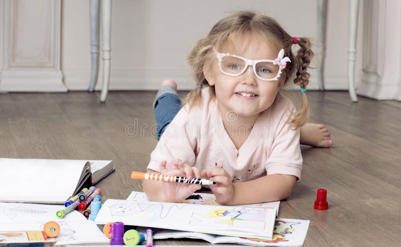 A menina está sentando-se em um assoalho e em uma tiragem fotografia de stock
