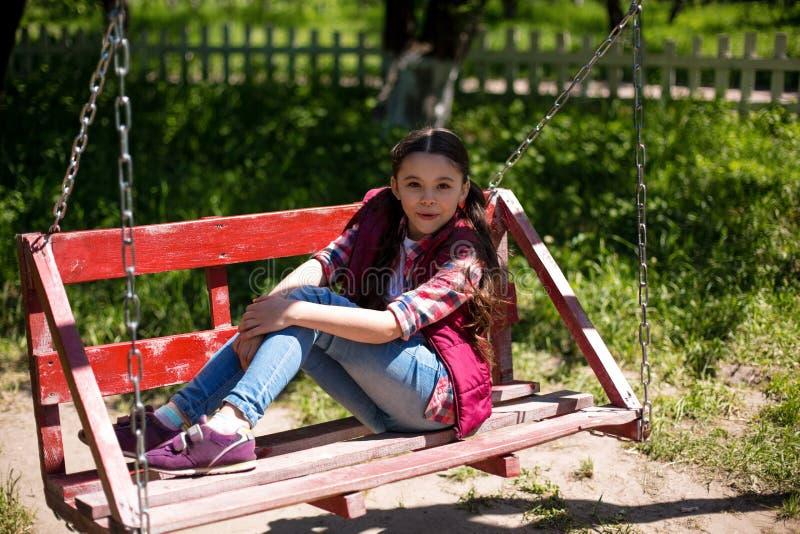 A menina está sentando-se em um balanço no parque foto de stock royalty free