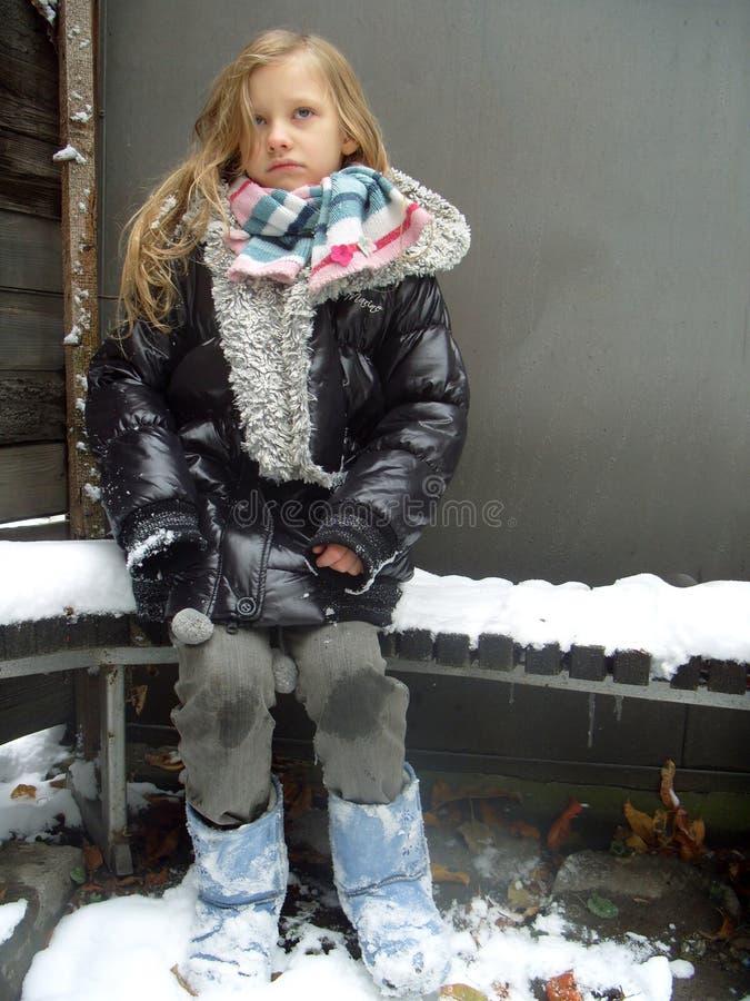 A menina está sentando-se em um banco em um winter imagens de stock royalty free