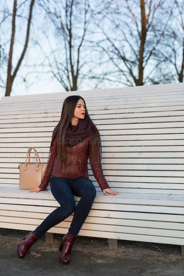 A menina está sentando-se em um grande banco branco Vestido nas calças de brim, em um casaco de cabedal e em botas imagens de stock