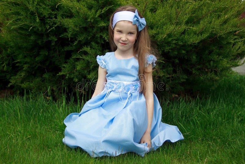 A menina está sentando-se em um prado verde fotos de stock royalty free