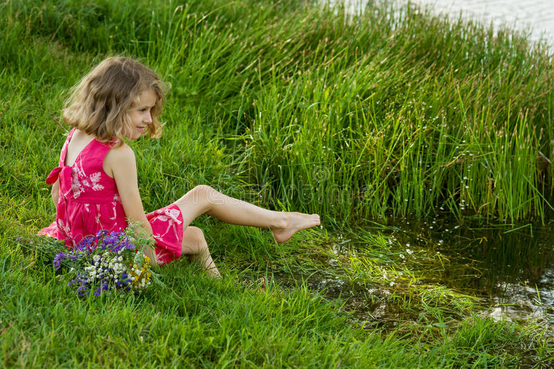 A menina está sentando-se na costa do lago foto de stock royalty free