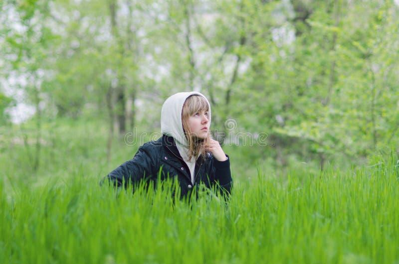 A menina está sentando-se na grama na clareira da floresta fotos de stock