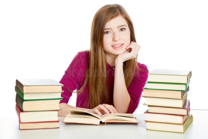 A menina está sentando-se na mesa e no livro de leitura imagens de stock royalty free