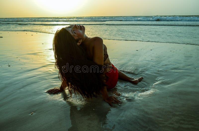 A menina está sentando-se na praia fotos de stock royalty free