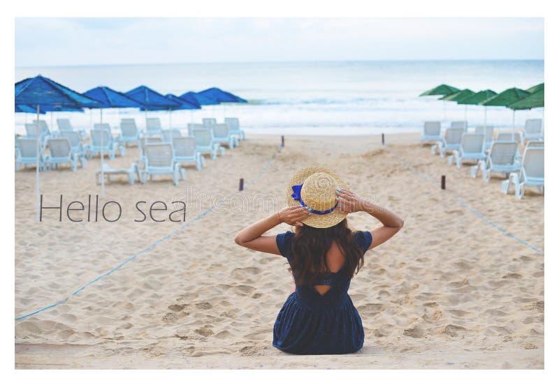 A menina está sentando-se na praia, a inscrição é cumprimentos ao mar imagens de stock royalty free