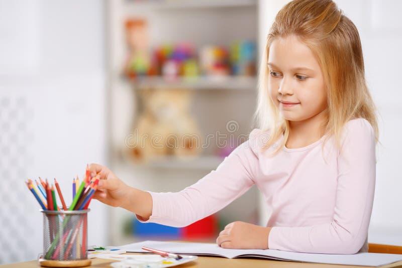 A menina está sentando-se na tabela e na tiragem fotografia de stock