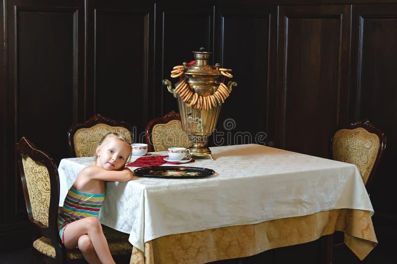 A menina está sentando-se na tabela para beber do chá imagem de stock