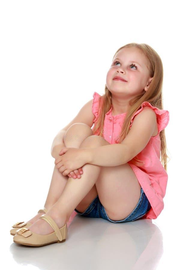 A menina está sentando-se no assoalho imagem de stock