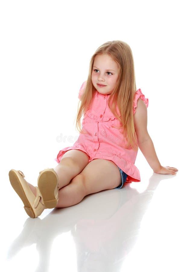 A menina está sentando-se no assoalho imagem de stock royalty free