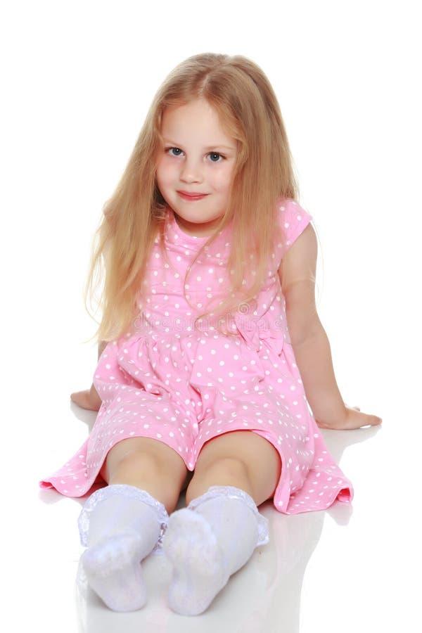 A menina está sentando-se no assoalho foto de stock royalty free