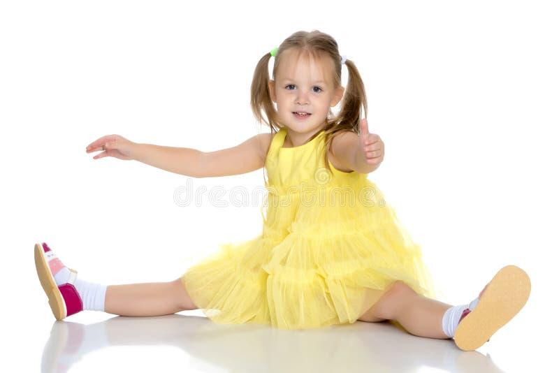 A menina está sentando-se no assoalho fotografia de stock