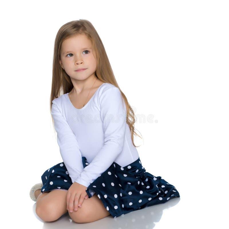 A menina está sentando-se no assoalho imagens de stock