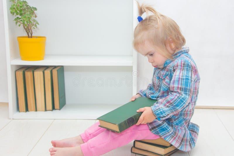 A menina está sentando-se no assoalho e manuseia um livro A criança foto de stock royalty free
