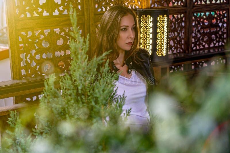 A menina está sentando-se no café com tela e lâmpada no fundo e com a planta verde no primeiro plano imagem de stock royalty free