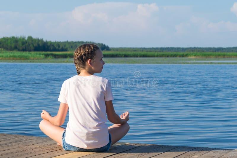 A menina está sentando-se no cais e está fazendo-se a ioga no tempo ensolarado contra um céu azul fotografia de stock royalty free