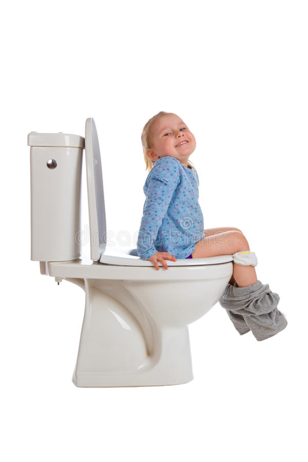 A menina está sentando-se no toalete fotografia de stock