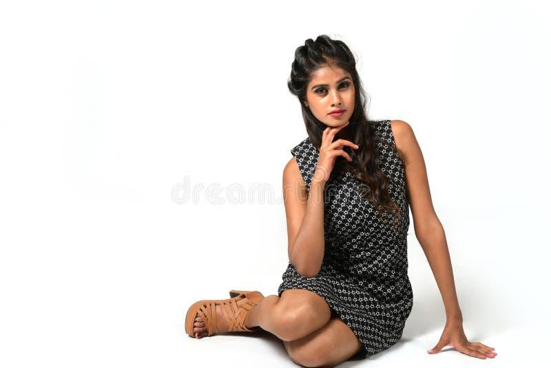 A menina está sentando-se no vestido preto no estilo fotografia de stock royalty free