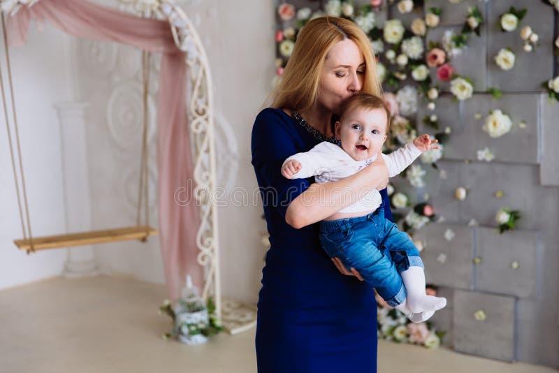 A menina está sentando-se nos braços de uma mulher em um vestido azul apertado e está tendo-se o divertimento que levanta acima d imagens de stock