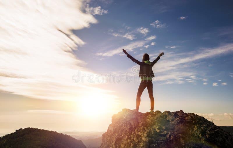 A menina está sobre a montanha e aprecia a vista do vale imagens de stock royalty free