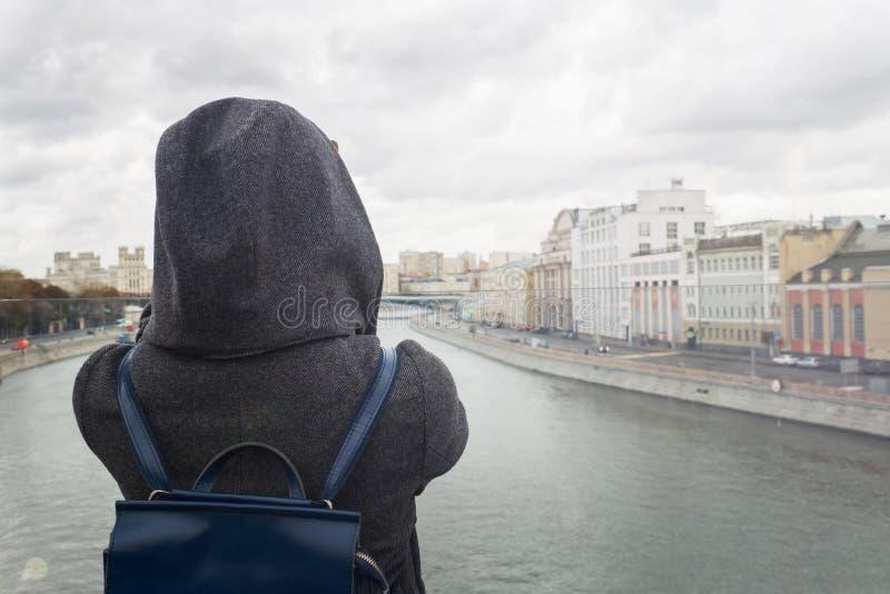 A menina está sozinha na ponte e olha para a frente ao centro de Moscou Estação do outono, estilo urbano fotografia de stock
