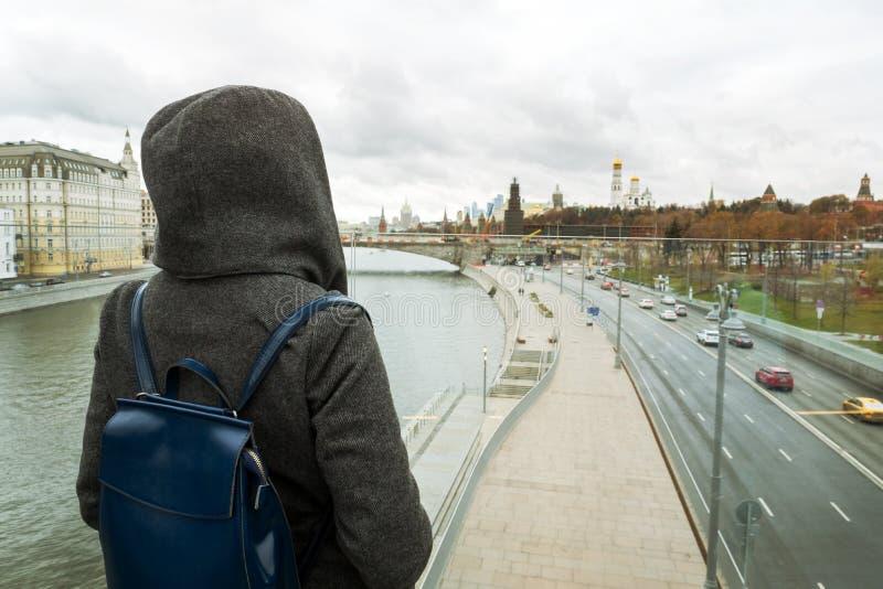 A menina está sozinha na ponte e olha para a frente ao centro de Moscou Estação do outono, estilo urbano foto de stock royalty free