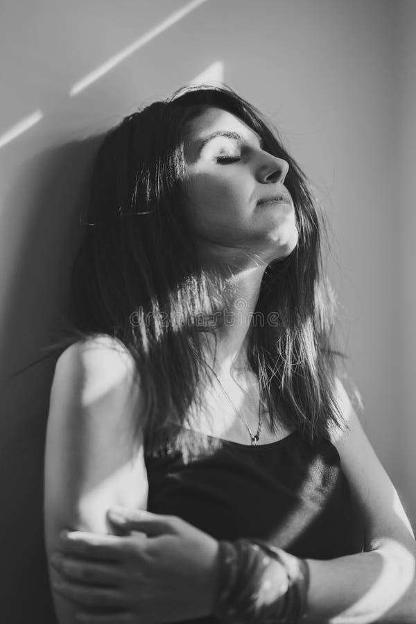 A menina está sozinha nas cortinas de janela Conceito preto e branco foto de stock