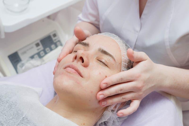 A menina está tendo um procedimento de limpeza da pele do ultrassom no salão de beleza fotografia de stock royalty free