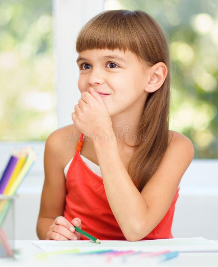 A menina está tirando usando lápis foto de stock royalty free
