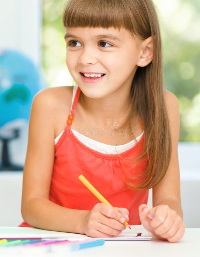 A menina está tirando usando lápis fotografia de stock royalty free