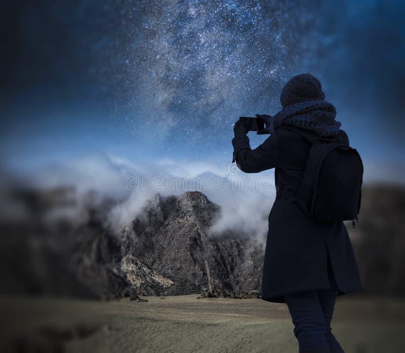 a menina está tomando imagens do céu noturno estrelado sobre o mounta foto de stock royalty free