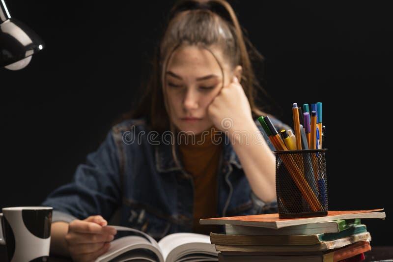 A menina est? sentando-se na tabela e no estudo fotografia de stock royalty free