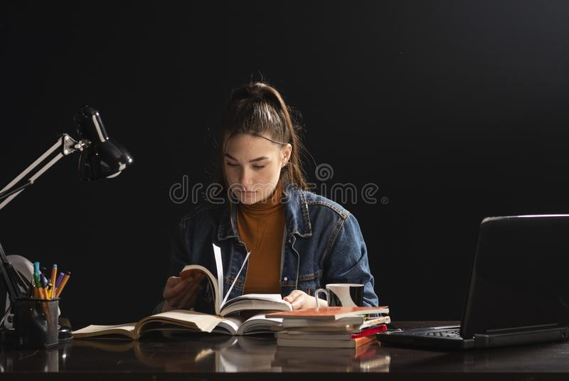 A menina est? sentando-se na tabela e no estudo fotos de stock royalty free
