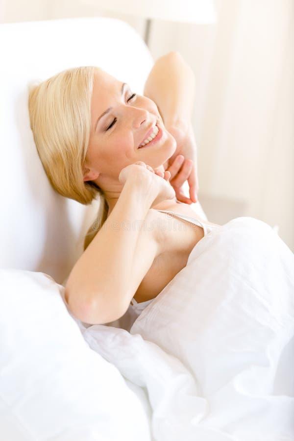 A menina estica-se que encontra-se na cama fotos de stock