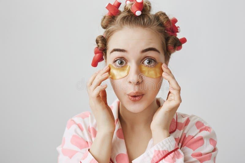 A menina europeia brincalhão engraçada nos cabelo-encrespadores, o nightwear e o olho remendam a máscara, expressando a surpresa  imagem de stock royalty free