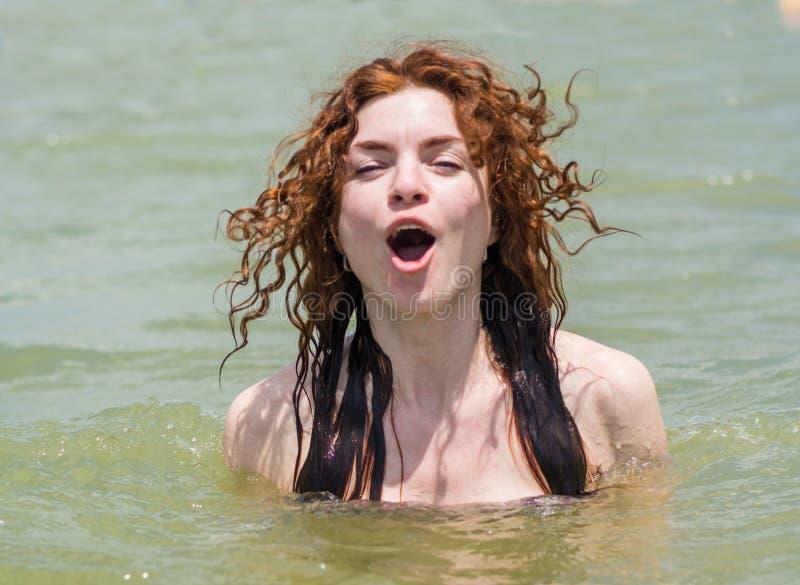Menina europeia nova bonita bonita que aprecia nadar no oceano fotografia de stock