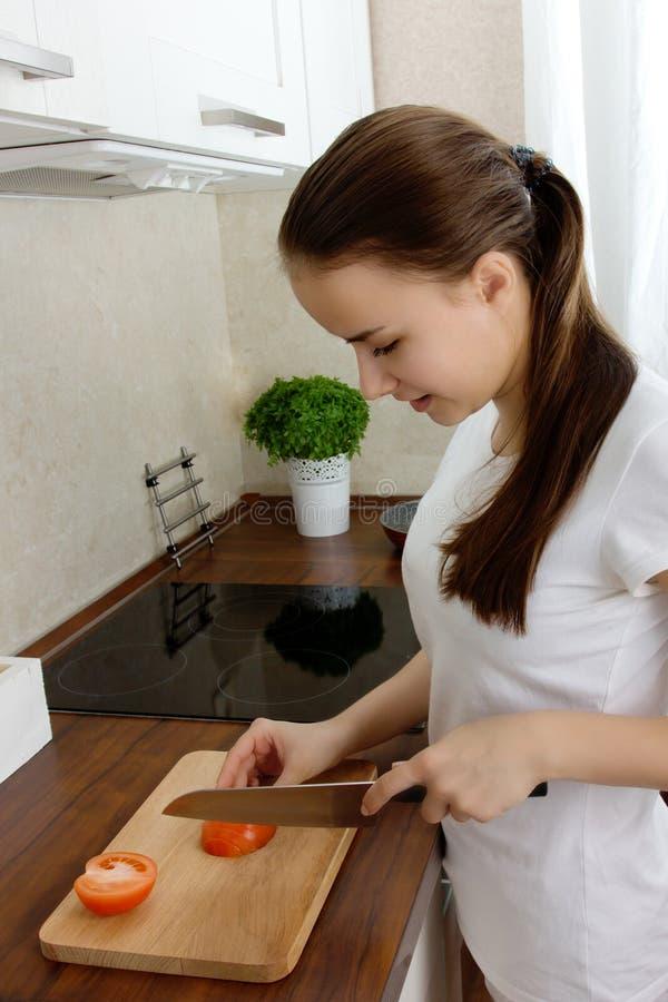 A menina europeia nova prepara o alimento fotografia de stock royalty free