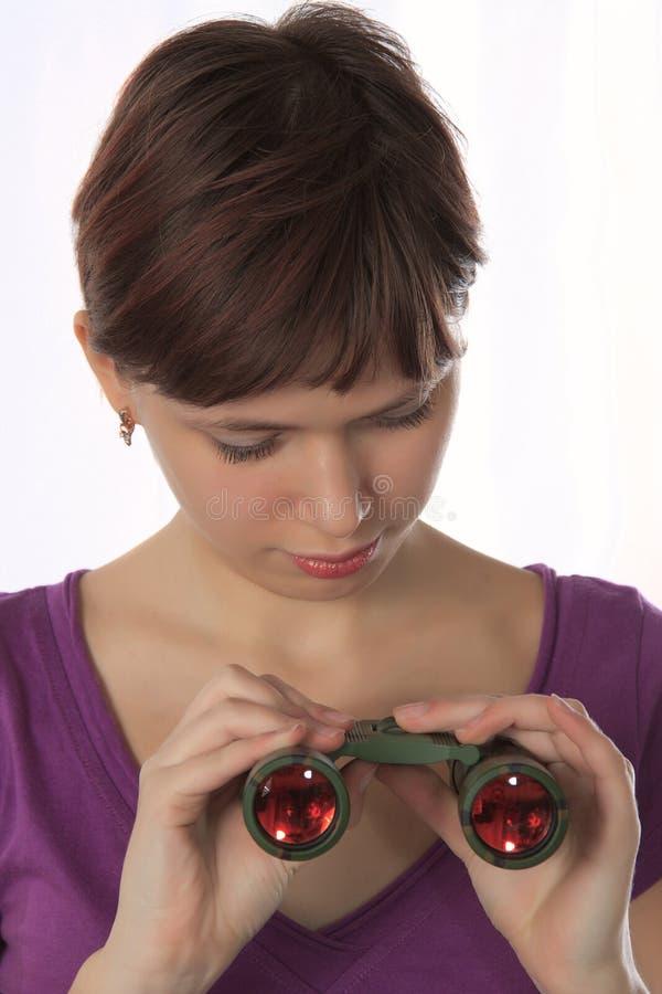 A menina examina os binóculos imagens de stock royalty free