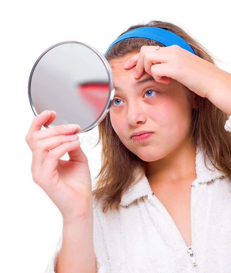 A menina examina suas espinhas no espelho fotografia de stock royalty free