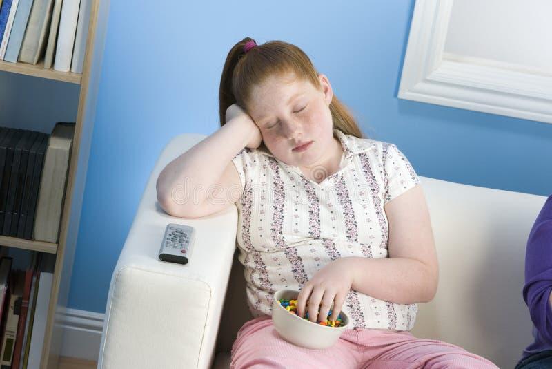 Menina excesso de peso que dorme no sofá imagens de stock royalty free