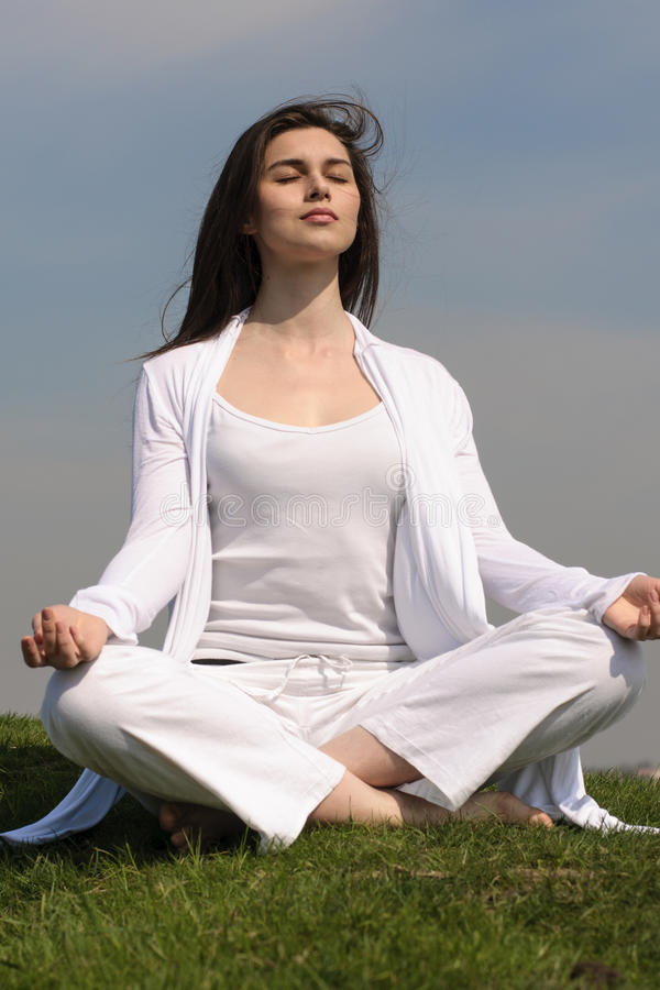 A menina executa a ioga no monte contra o céu azul imagens de stock royalty free