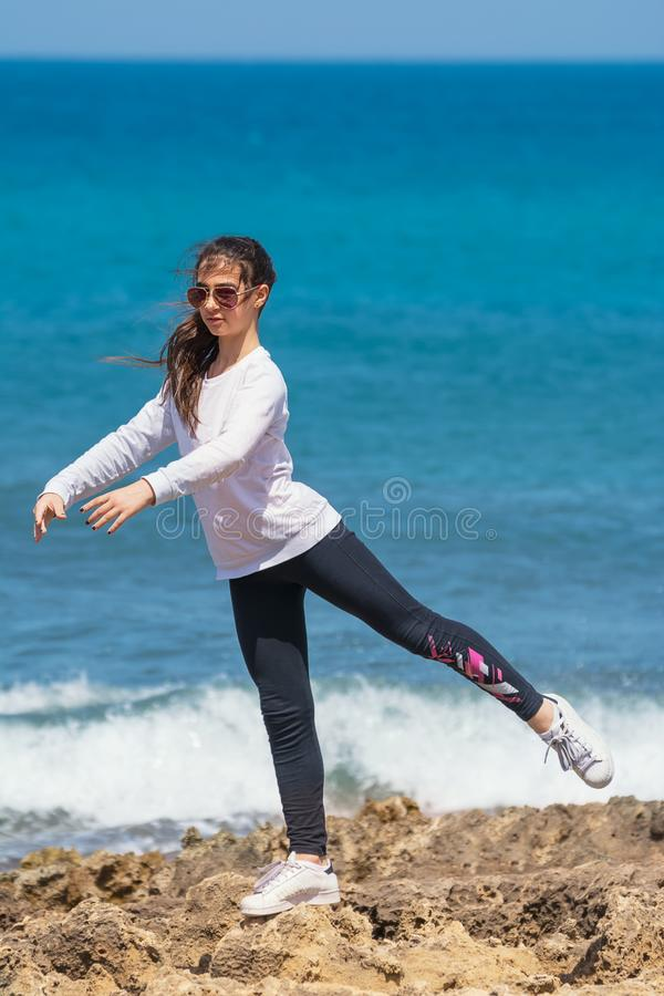 A menina executa o Arabesque nas rochas do mar imagens de stock