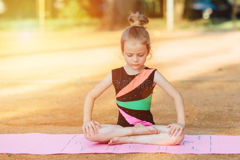 A menina executa o exercício ginástico no ar fresco fotografia de stock