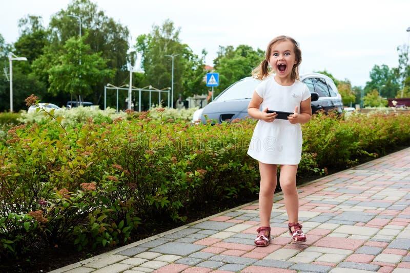 Menina expressivo adorável com um smartphone imagem de stock
