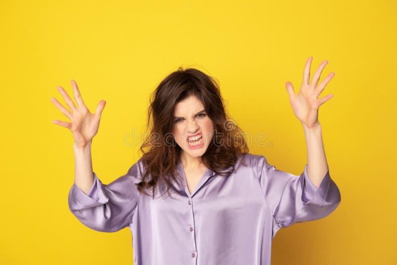 Menina expressivo irritada nos pijamas isolados no amarelo foto de stock