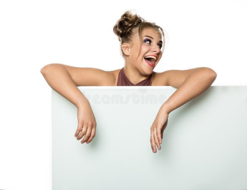 Menina expressivo que está de trás e que inclina-se em um quadro de avisos ou em um cartaz vazio branco, espaço da cópia para seu imagem de stock